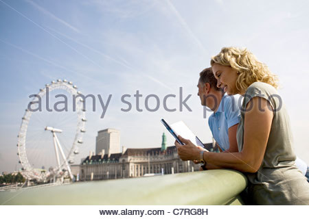 A middle-aged couple standing near the London Eye, looking at a guidebook - Stock Photo