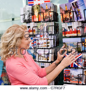 A middle-aged woman looking at postcards outside a souvenir shop - Stock Photo
