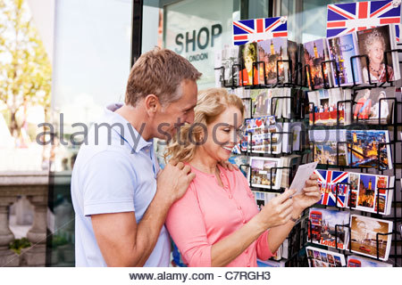 A middle-aged couple looking at postcards outside a souvenir shop - Stock Photo
