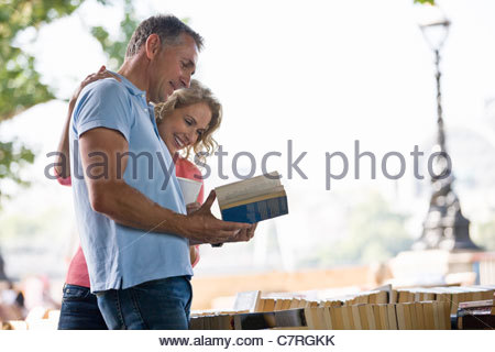 A middle-aged couple looking at books at a book stall - Stock Photo