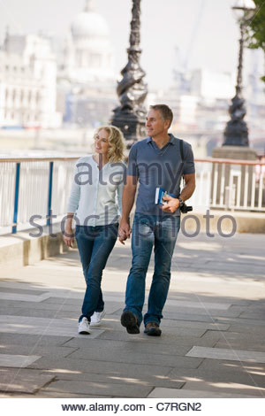 A middle-aged couple walking hand in hand, next to the river Thames - Stock Photo