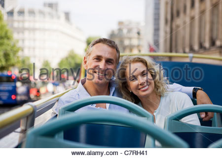 A middle-aged couple sitting on a sightseeing bus, embracing - Stock Photo