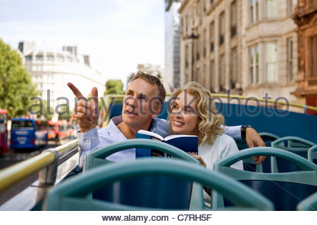 A middle-aged couple sitting on a sightseeing bus, admiring the view - Stock Photo