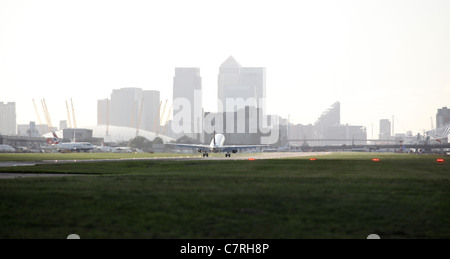 A Boeing 318 aircraft taking off from London City Airport with a view of the City of London in the background - Stock Photo