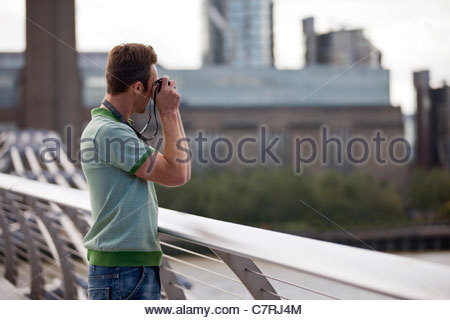 A mid-adult man standing on the Millennium Bridge, taking a photograph - Stock Photo
