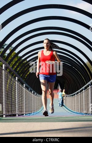 Female jogger, runner, on a pedestrian bridge. Bridge called 'Slinky Springs to fame', 450 meter long bridge is - Stock Photo