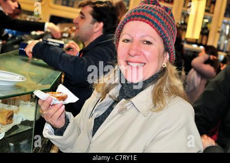 Portugal, Lisbon: Lady from Brazil trying  the famous 'Pasteis de Belém' in the Antiga Confeitaria de Belém - Stock Photo