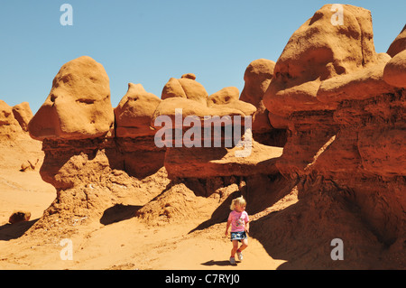 A little girl walks near weirdly shaped rocks in Goblin Valley State Park, Utah - Stock Photo