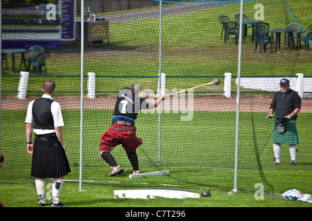 Gregor Edmunds, heavyweight athlete and strong man,  throwing the hammer at Cowal Highland Gathering, 2011, Dunoon. - Stock Photo