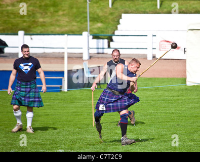 Kilted 'heavy' athlete throwing the hammer (Scots Style), wearing special, bladed shoes.  Cowal Highland Gathering - Stock Photo
