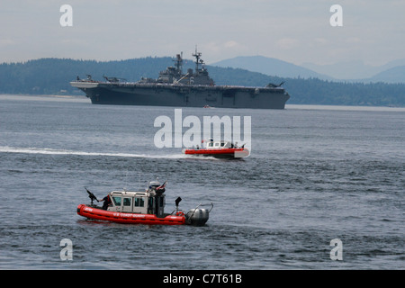 US Coast Guard patrol boats securing the way for the Amphibious Assault Ship the USS Bonhomme Richard LHD-6 to dock - Stock Photo