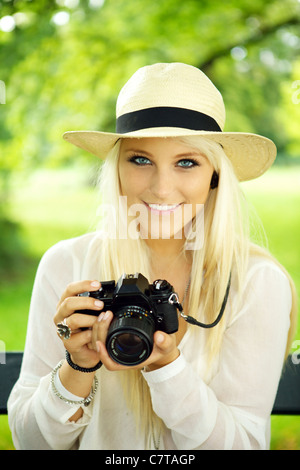 Portrait of a cute girl with an old-fashioned SLR camera.  - Stock Photo