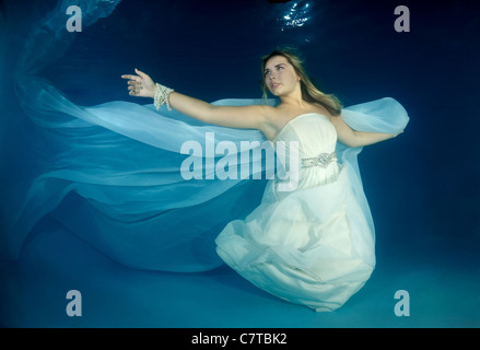 A young woman with big hair posing in a pool underwater - Stock Photo