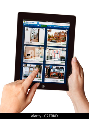 Hands holding iPad searching for a house for sale on the Rightmove app on a tablet - Stock Photo