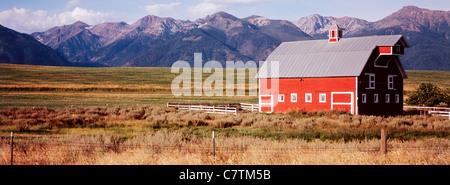 Red wooden barn in field and Wallowa Mountain range near Joseph in Eastern Oregon USA - Stock Photo