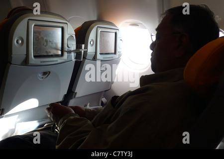 Man in airplane during flight - Stock Photo