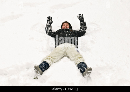 Boy lying down in the snow - Stock Photo