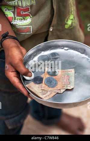 Young poor lower caste Indian street boy begging with money plate. Andhra Pradesh, India. selective focus - Stock Photo