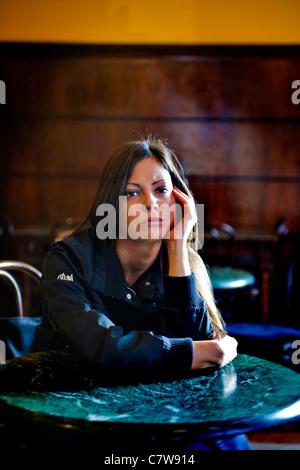 Pensive woman sitting at bar - Stock Photo