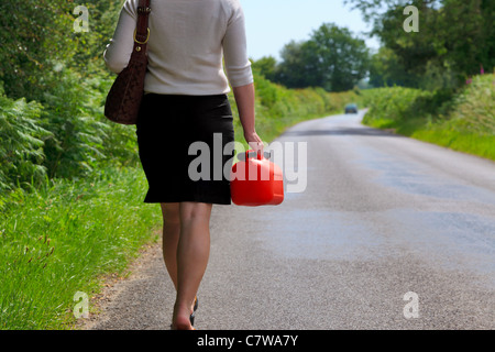 Photo of a woman who's vehicle has broken down walking along a country lane with a spare fuel can in her hand. - Stock Photo