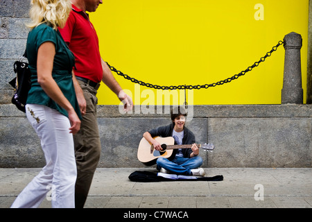 Teenage boy playing guitar in the street - Stock Photo
