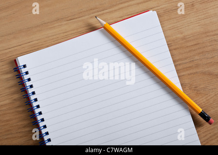 Photo of a blank ruled notepad and pencil on a desk, add your own copy. - Stock Photo