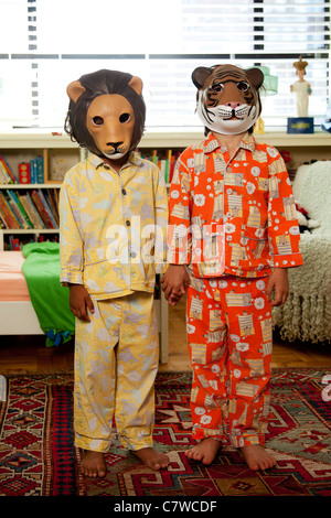 Two kids with masks on in pajamas - Stock Photo