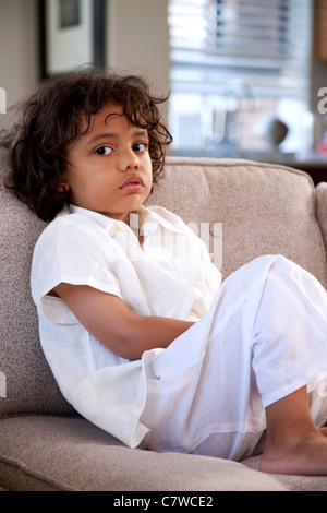 young boy sitting on the couch in pajamas - Stock Photo