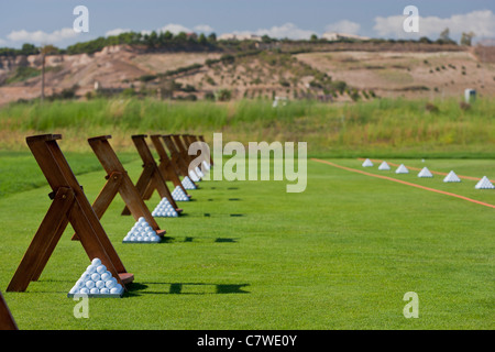 Pyramids of golf balls at a Golf driving practice range - Stock Photo