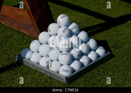 Pyramid of golf balls at a Golf driving practice range - Stock Photo