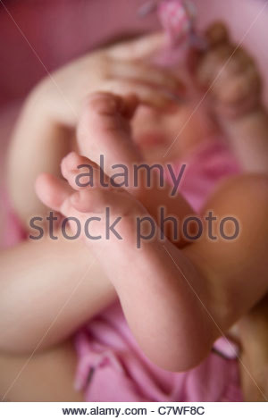 Close up of baby feet lying in crib - Stock Photo