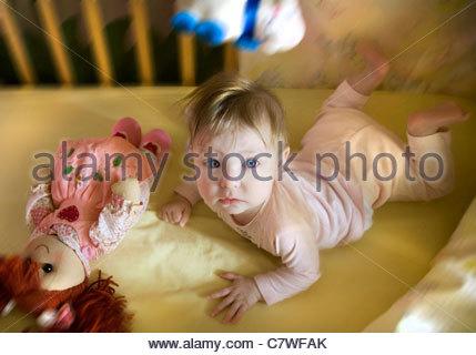 Portrait of girl lying in crib - Stock Photo