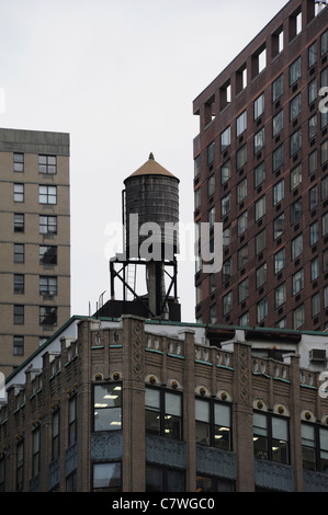 Tower block with strip light windows and wall corner rooftop water tank below tall skyscrapers, Columbus Circle, - Stock Photo