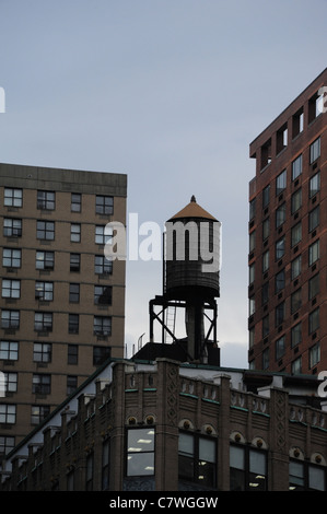 Traditional wooden water tank standing on rooftop corner tower block, overlooked by skyscrapers, Columbus Circle, - Stock Photo