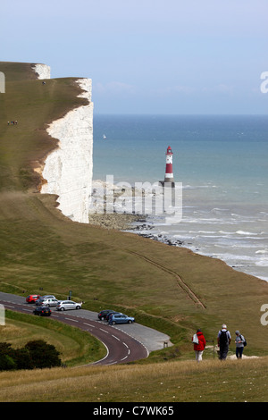 People walking along coast path, Beachy Head lighthouse in background , near Eastbourne , East Sussex , England - Stock Photo