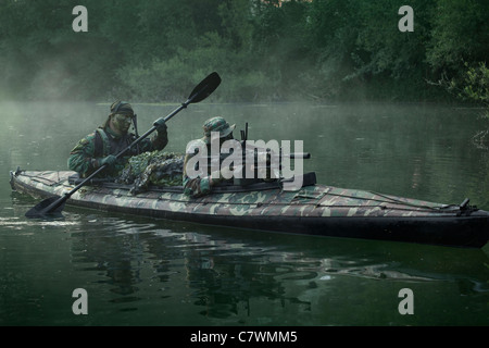 Navy SEALs navigate the waters in a folding kayak during jungle warfare operations.