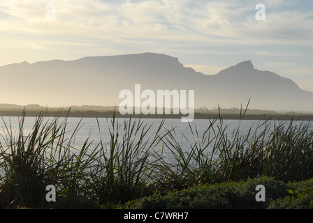 view across lake to mountains at dusk,  near Cape Town, Western Cape, South Africa - Stock Photo