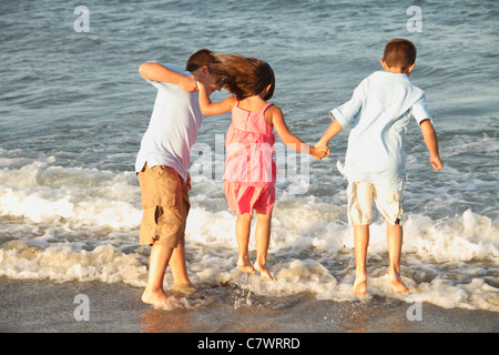 Kids on the beach jumping the waves girl and boys - Stock Photo