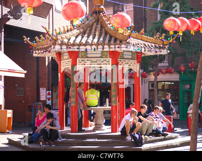 People sitting around a pagoda in Newport Street in London's Chinatown - Stock Photo