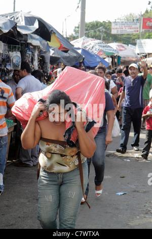 Managua Nicaragua Mercado Oriental flea market marketplace shopping purchase Hispanic woman carrying parcel on back - Stock Photo
