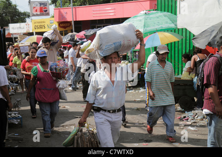 Managua Nicaragua Mercado Oriental flea market marketplace shopping vendor stall purchase Hispanic man woman carrying - Stock Photo