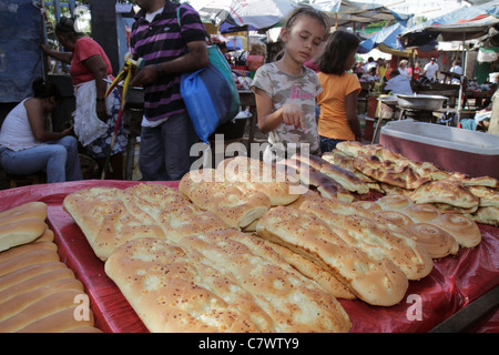 Managua Nicaragua Mercado Oriental flea market marketplace shopping food vendor stall display bread loaf baked goods - Stock Photo