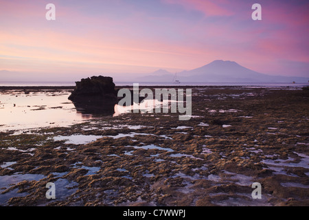 Mushroom Bay at sunset with Mount Agung in the background, Nusa Lembongan, Bali, Indonesia - Stock Photo