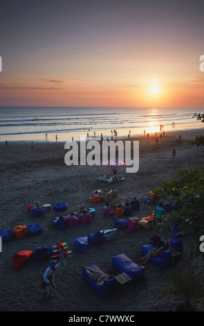 People sitting at Crystal Palace restaurant on Legian beach at sunset, Bali, Indonesia - Stock Photo