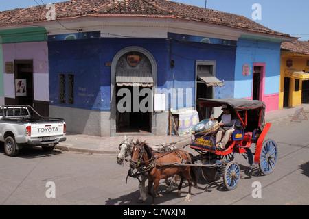 Nicaragua Granada Calle Vega colonial heritage neighborhood street scene corner building business colorful roof - Stock Photo