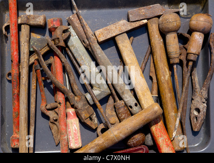 aged weathered rusty hand tools in black iron tray - Stock Photo