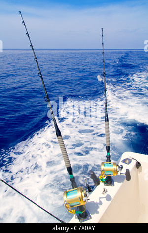 boat fishing trolling in deep blue sea with rods and reels - Stock Photo