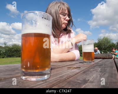 Thoughtful woman in a beer garden on a sunny day with two half full glasses of beer on the plain wooden table - Stock Photo