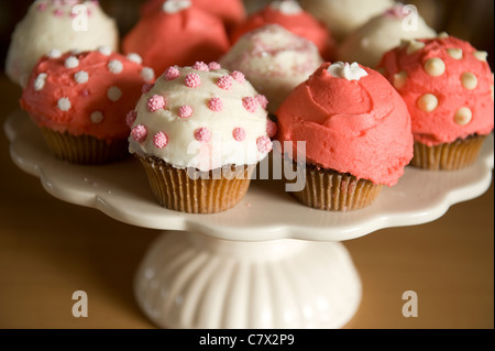 cupcakes frosted pink and white various designs on cake plate and countertop backlit - Stock Photo