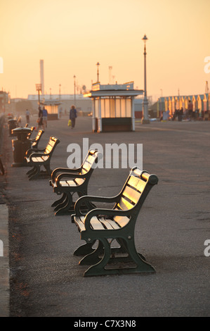 Back lit benches on the Brighton and Hove seafront during dusk, Hove, East Sussex, UK - Stock Photo